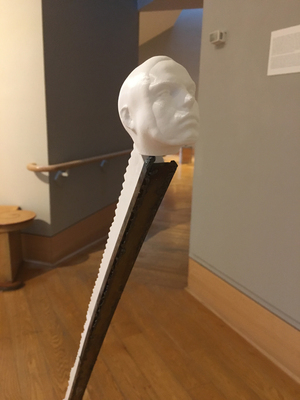 3D printed face connected to a long row of stairs in white